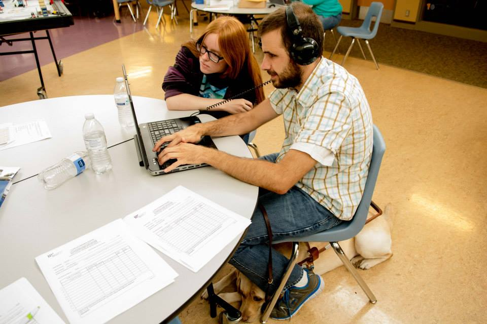 A red-headed woman with long hair and glasses sits at a table with a bearded man wearing headphones, both are looking at his laptop screen. A guide dog is curled up below the man's chair.