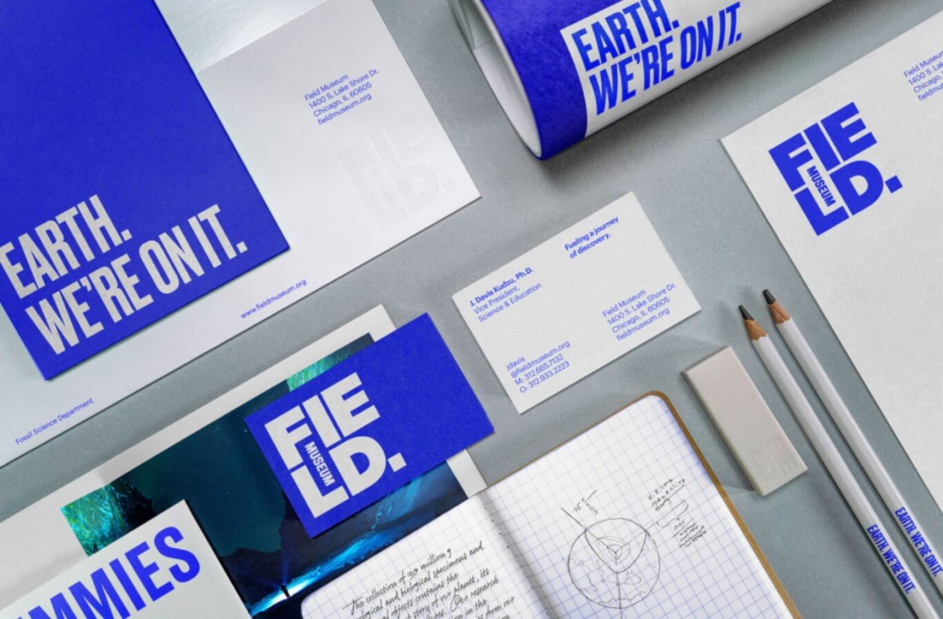 Bright blue and white Field Museum–branded business cards, notecards, pencils, and letterhead are neatly laid out on top of a grey surface.