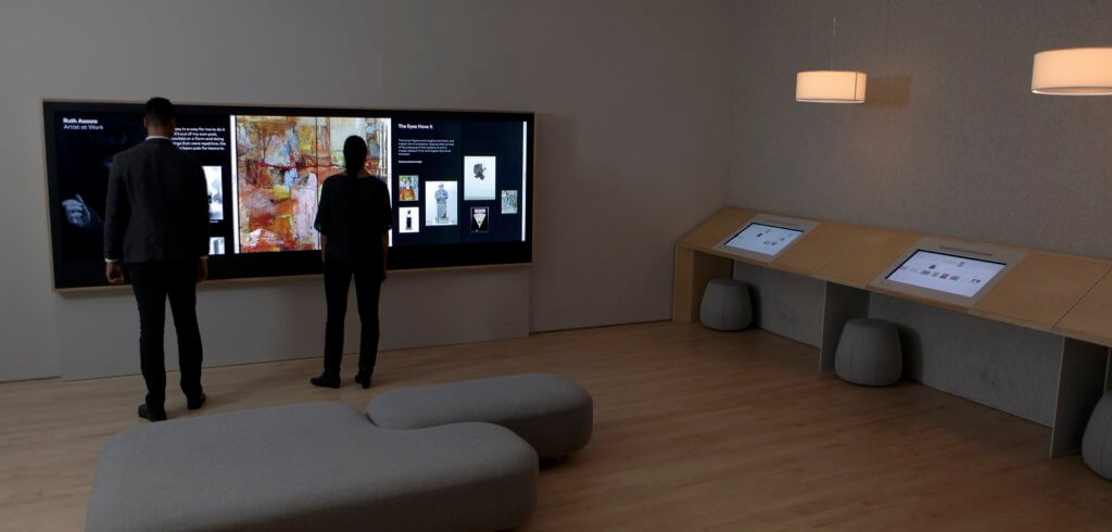 Two people stand in front of a large multi-person, multitouch interface composed of three vertical touchscreens placed side-by-side to form a touchable wall of art in the San Francisco Museum of Modern Art.