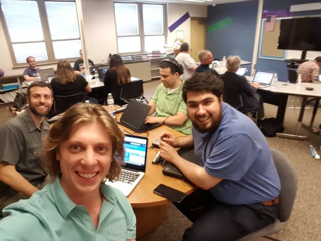 A selfie of Sina and three other people all smiling broadly with laptops sitting at a round table in a computer lab.