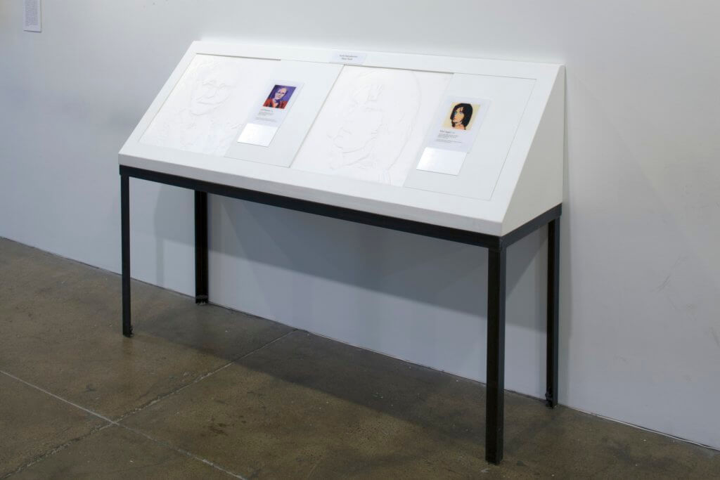 Two tactile images of Andy Warhol paintings are displayed with braille descriptions and a color reproduction of the artwork on a table that is tilted up in a 45 degree angle from the wall to ease the user when they touch the images.