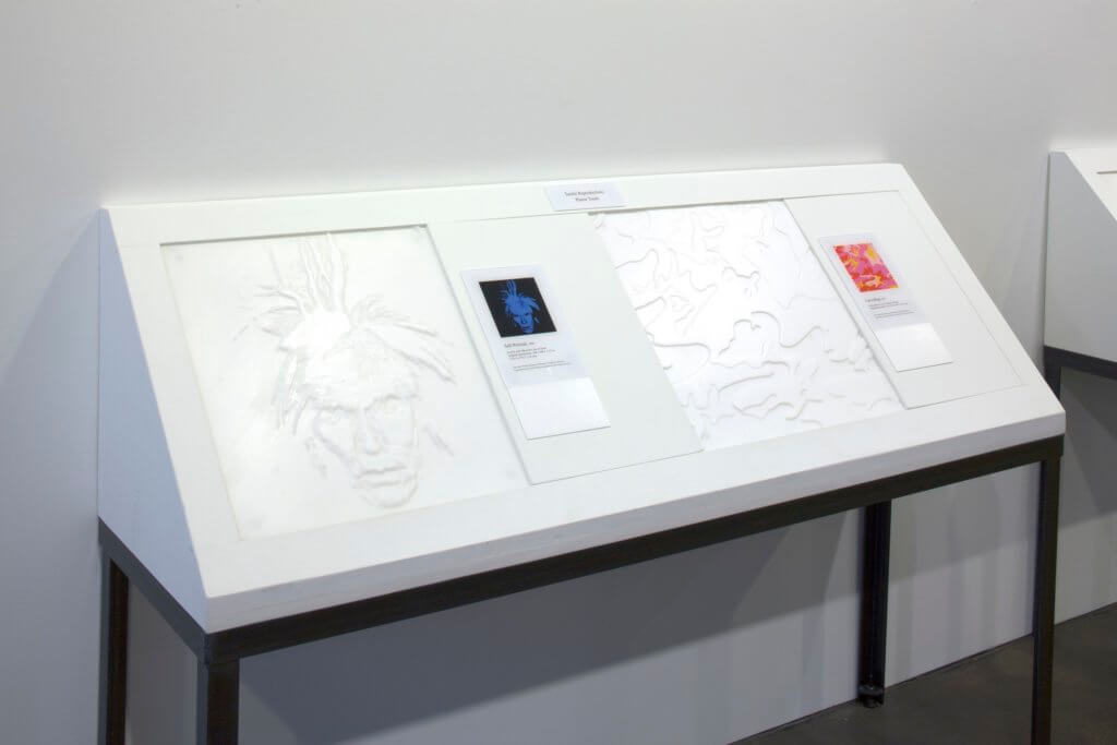 Two tactile images of two Andy Warhol painting are displayed with braille descriptions and a color reproduction of the artworks on a table that is tilted up in a 45 degree angle from the wall to ease the user when they touch the images.