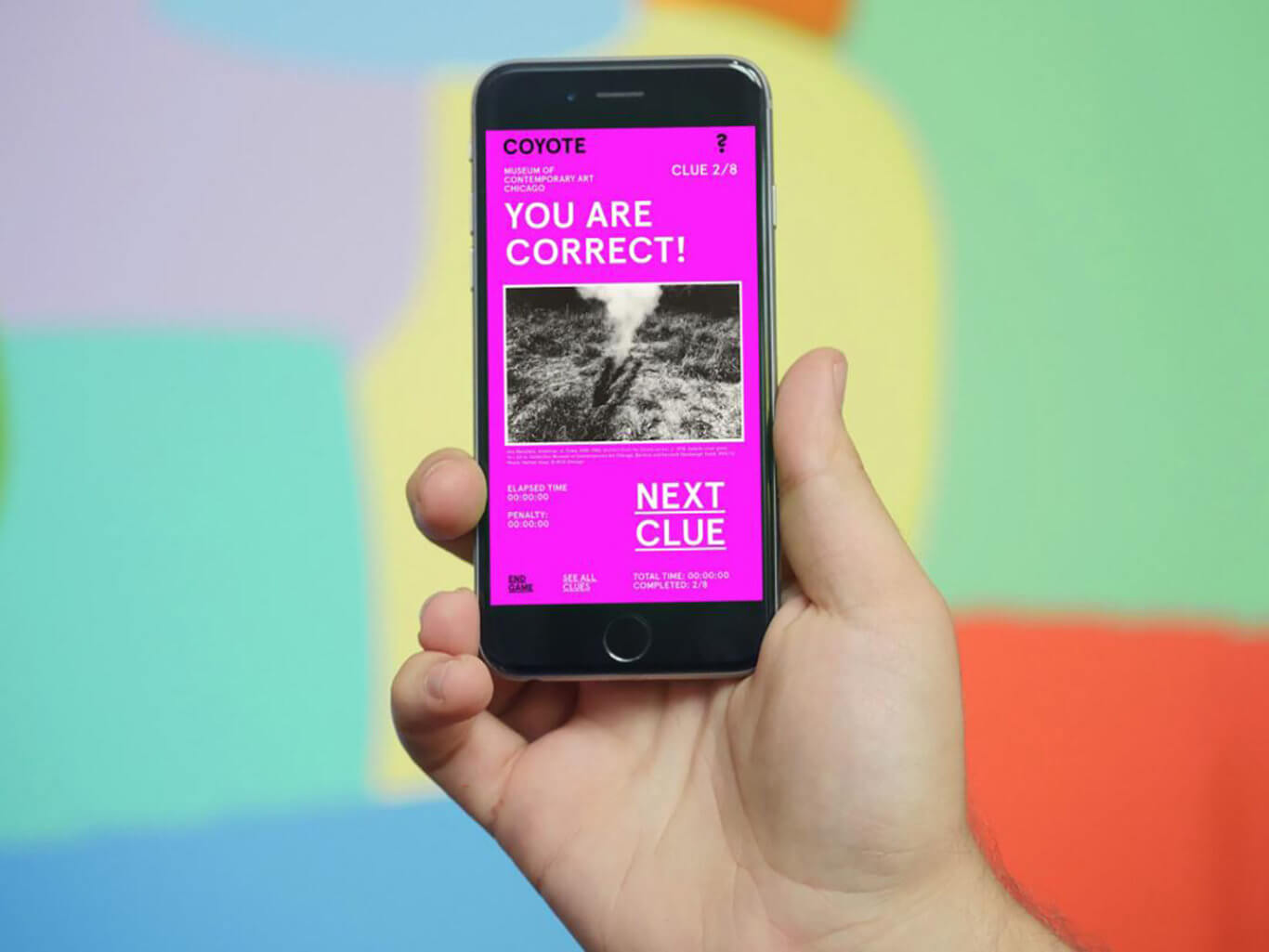 """A light-skinned hand holds up a smartphone with the screen facing you. The screen reads, """"YOU ARE CORRECT!"""" at the top and """"NEXT CLUE"""" in the bottom right-hand corner."""